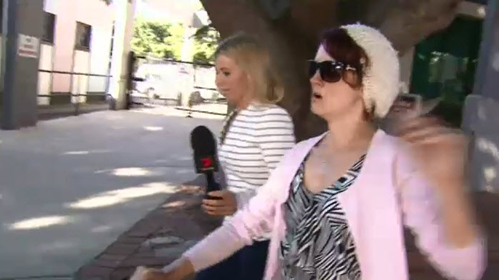 The woman allegedly stubbed the lit cigarette into Bernhardt's face outside court. (9NEWS)