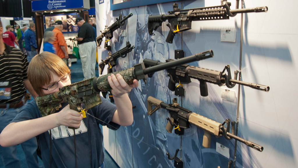 A young man who chose not to give his name sizes-up an assault style rifle during the National Rifle Association's annual convention in Houston. (AP)