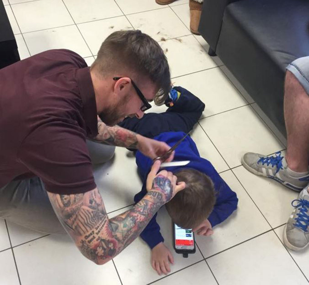 Barber goes to extreme lengths to make boy with autism comfortable during haircut