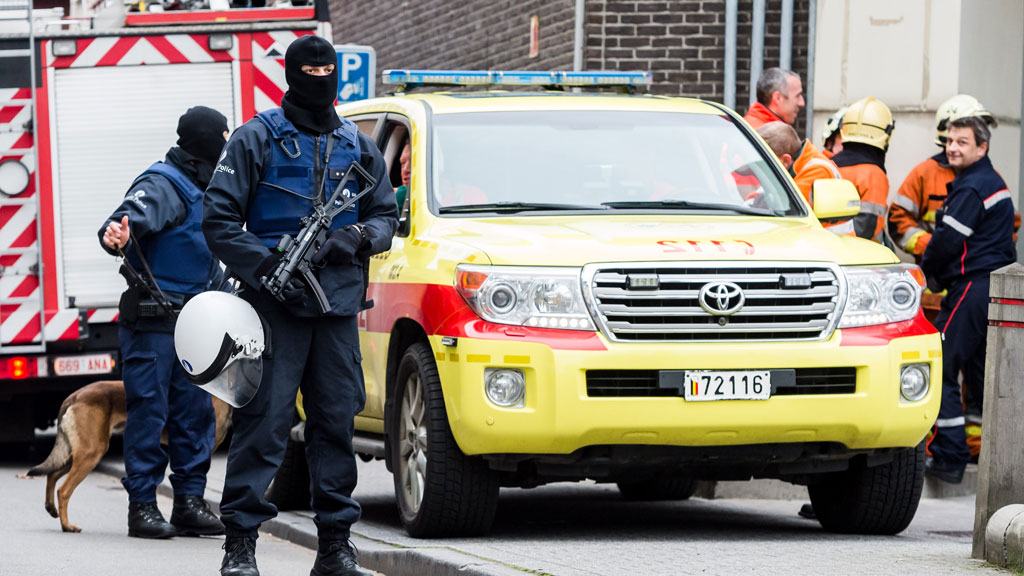 Heavily-armed forces carry out major raids in Brussels, as police release five of seven Paris attacks suspects
