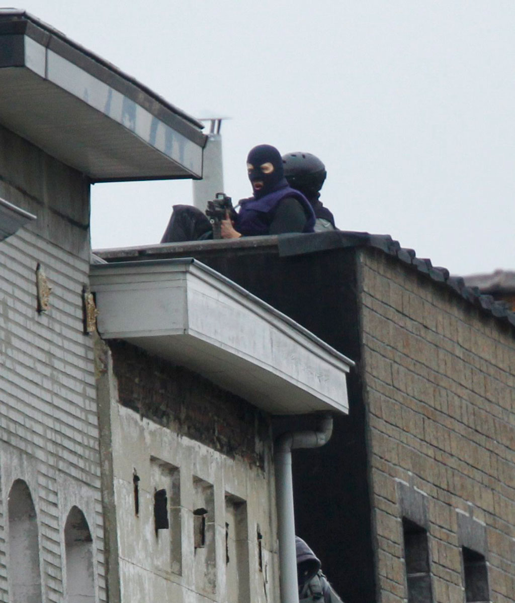 Snipers stand at rue Delaunoy during highly-targeted raids in the district of Molenbeek, Brussels. (AAP)