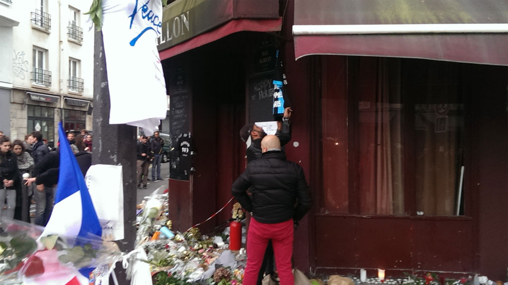 Two men hang a football t-shirt on the awning of the Le Carillon restaurant. (Jack Hawke)