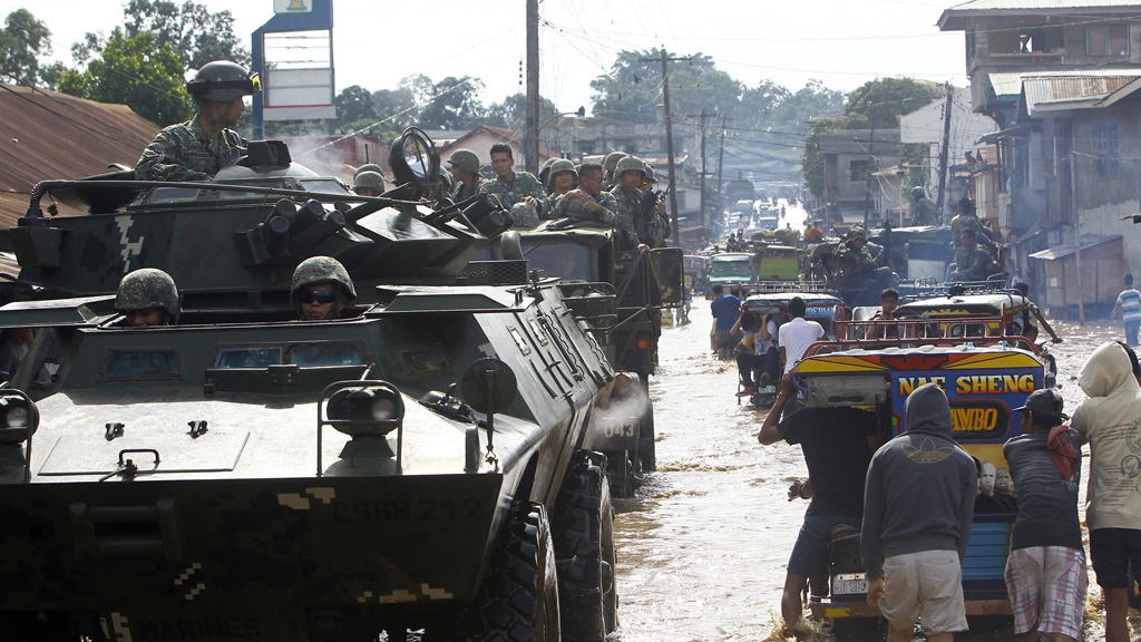 Filipino soldiers on a tanks and military trucks conducting patrol on a flooded community in Jolo, Sulu island, southern Philippines. (AAP)