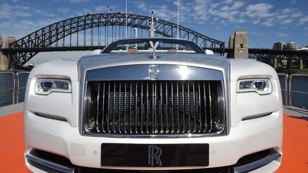 Rolls-Royce has rolled out its new super-luxurious car in style by unveiling it on top of a superyacht on Sydney Harbour. (AAP)