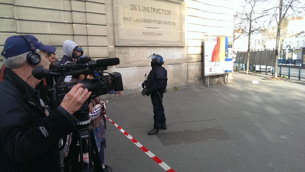 A heavily-armed policeman stands guard near the scene of the raid. (Jack Hawke, 9news.com.au)