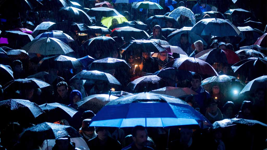 People stand under umbrellas as rain falls during a candlelight vigil to honour the victims of the Paris terrorist attacks, in Vancouver, B.C. (AAP)
