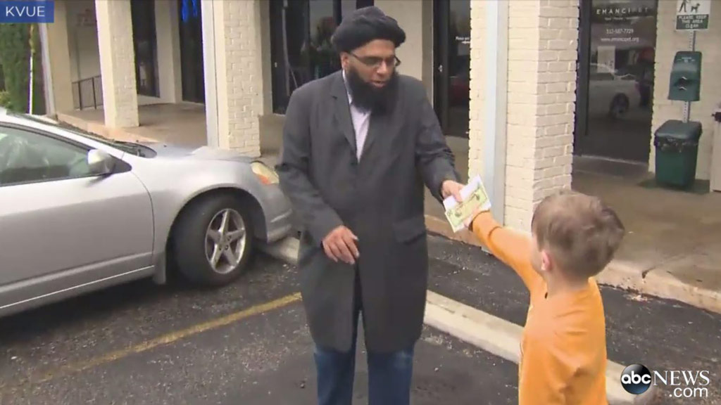 Jack hands his piggy bank savings to Faisal Naeem (Image: KVUE)