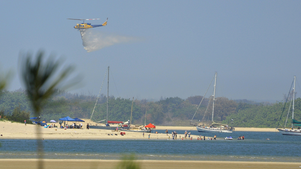 A helicopter water-bombs The Spit. (Supplied / Tim Cram)