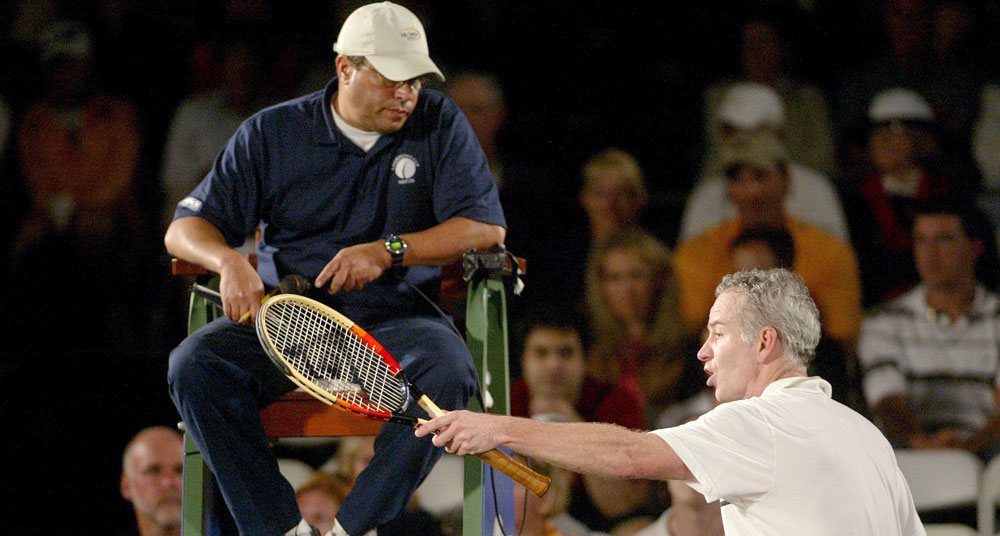 John McEnroe argues with an umpire. (Getty)