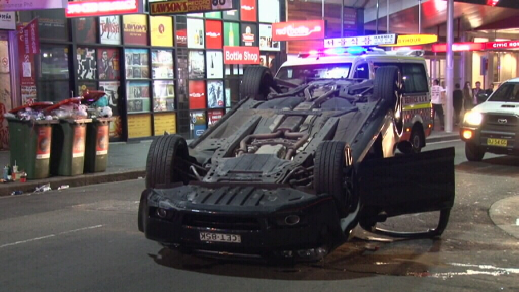 Two men escape car rollover without injury in Sydney CBD