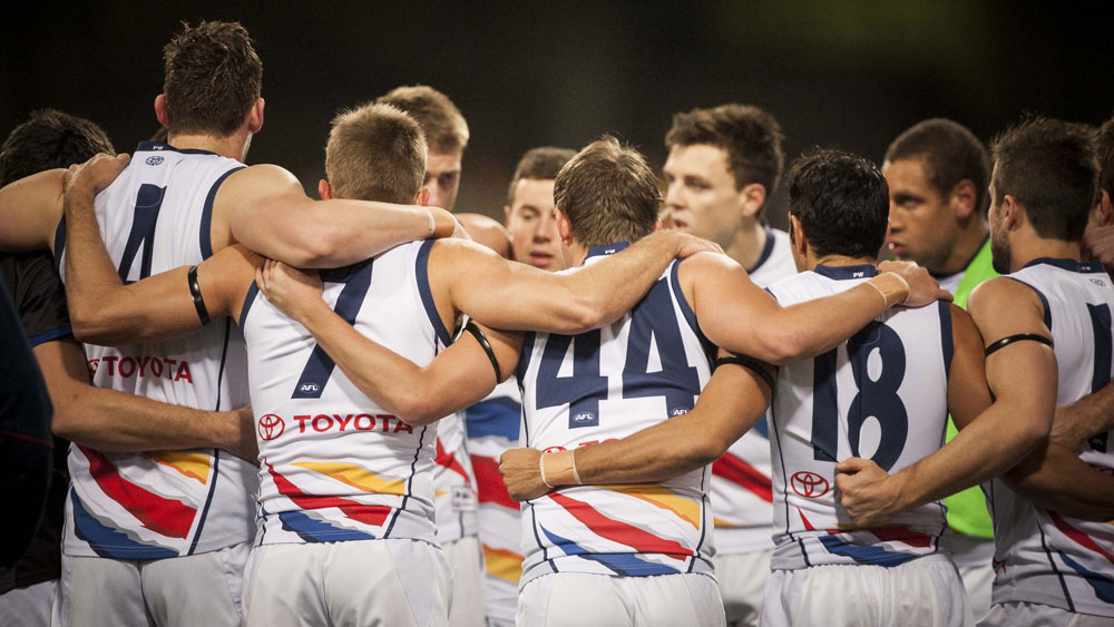 Adelaide Crows players in a huddle. (AAP)