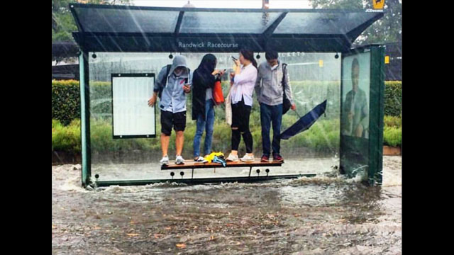 Wild storms have smashed Sydney today, with a tornado wreaking havoc at Kurnell in the city's south.<br /><br />In this photo, a group is forced to stand on the bench of a bus stop at Randwick Racecourse to escape the flooding. (Shaun Wellfare, 9NEWS)