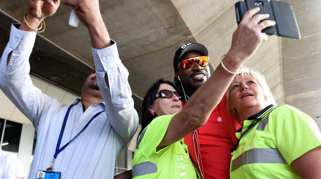 Chris Gayle poses for selfies with Melbourne airport staff yesterday. (AAP)