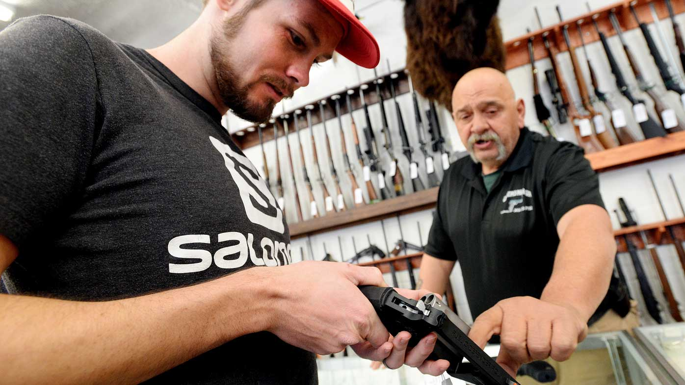 Bill Karnok, right, of Grandpa's Pawn Shop in Longmont, Colo., shows Shane Angelovich a gun that he is interested in buying on Tuesday. (AAP)