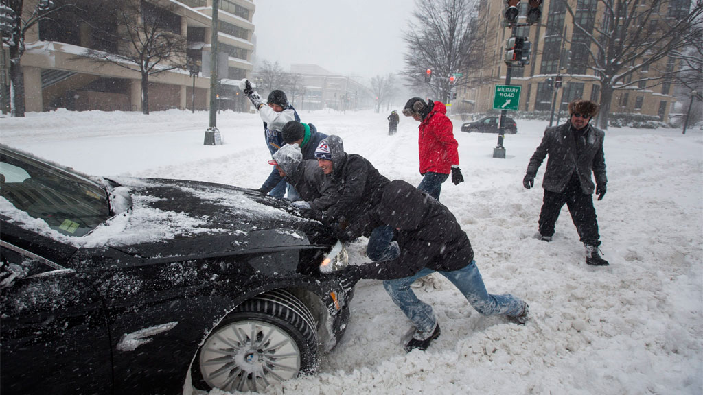 Pedestrians help push out a commuter's car during a major blizzard. (AAP)