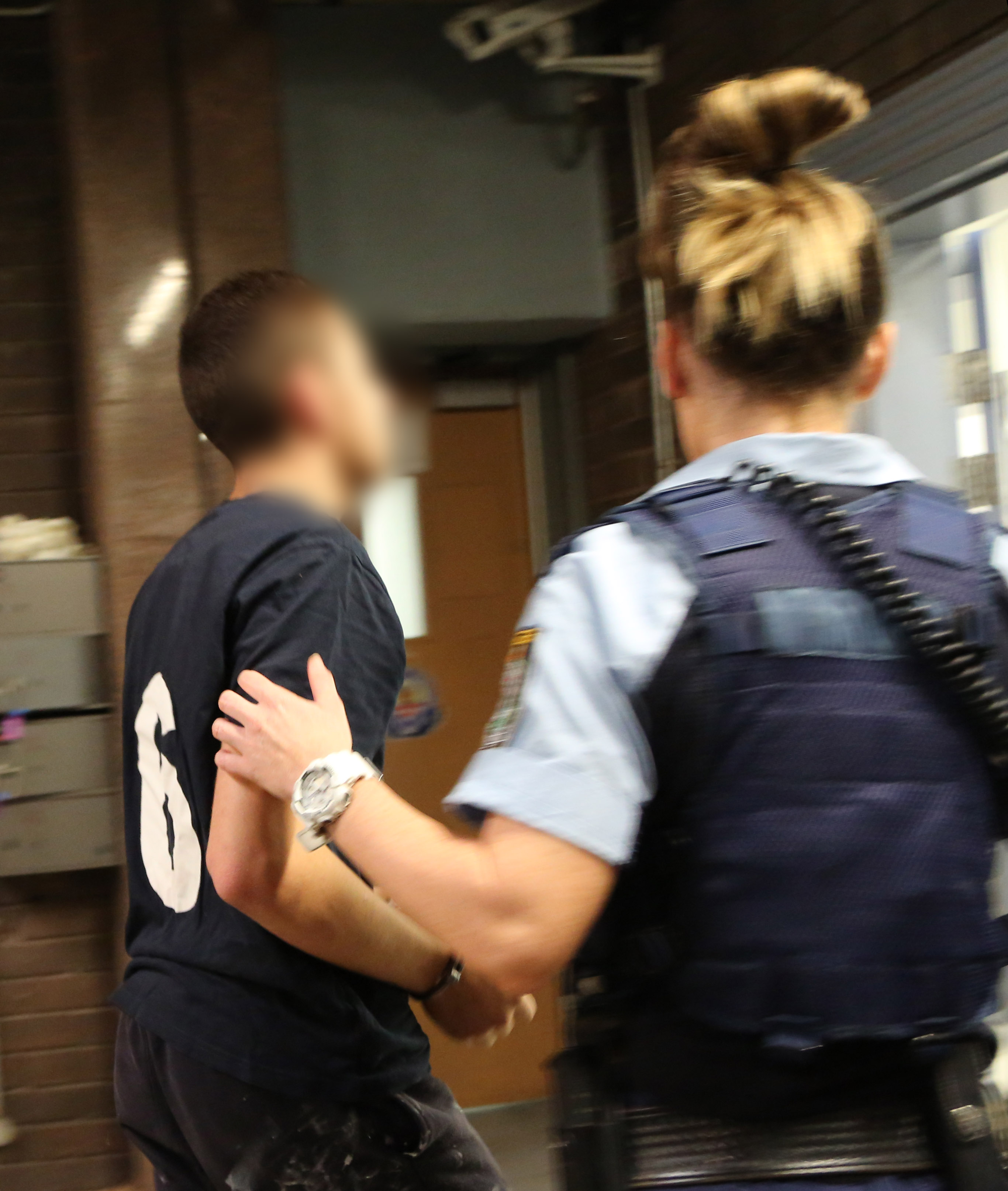 Police leading one of the accused into the station. (NSW Police Force)