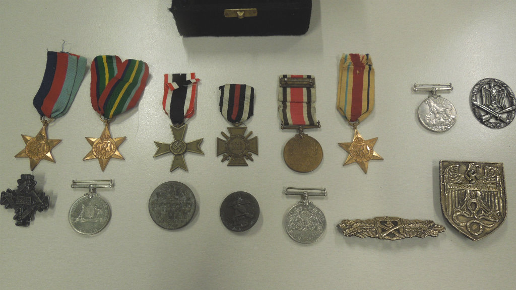 Stolen war medals found alongside drugs and firearms during police search of Sydney motel room