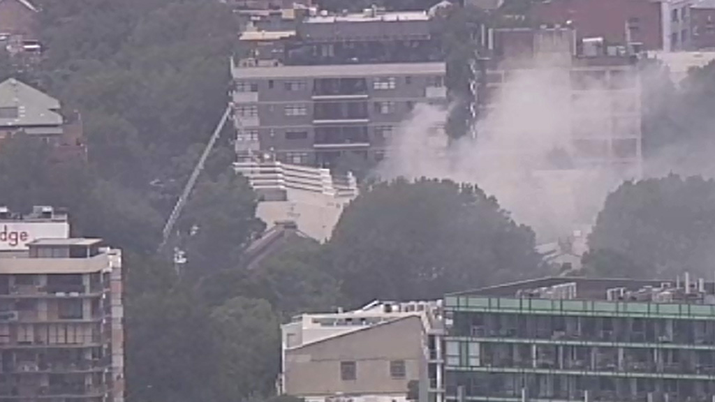 Fire crews use ladders to rescue two people from burning terrace in Surry Hills, Sydney