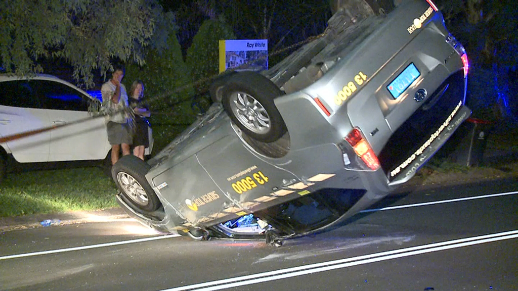 Taxi driver crashes into two parked cars and flips cab in Sydney's north-west