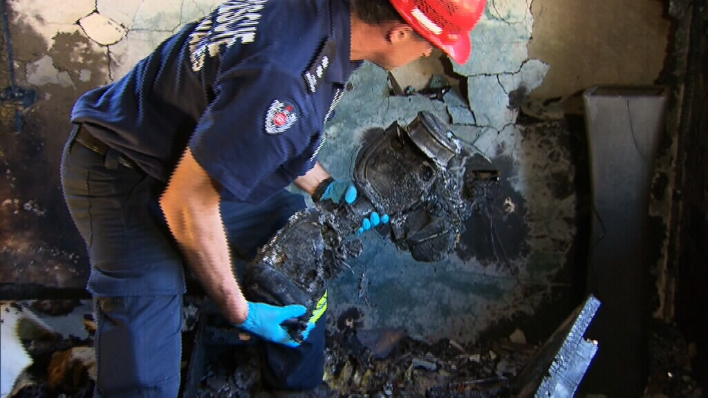A fire investigator with the charred remains of the hoverboard that caused the fire.