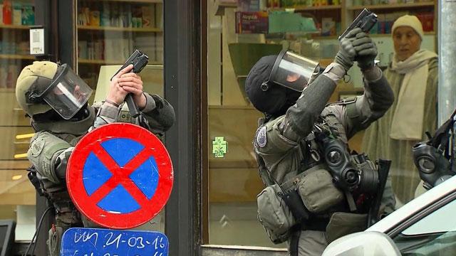 Armed police officers take part in a raid in the Molenbeek neighborhood of Brussels, Belgium. (AAP)