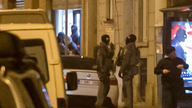 Belgian special intervention forces leave a house after a raid in the Molenbeek neighborhood. (AAP)