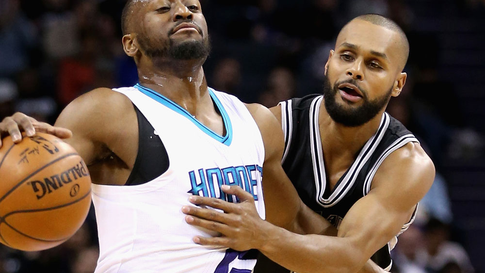 Patty Mills (R) defends the Spurs. (AFP)