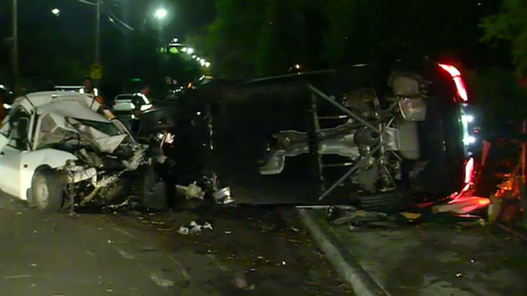 The BMW flipped onto its side after crashing into three parked cars. (9NEWS)