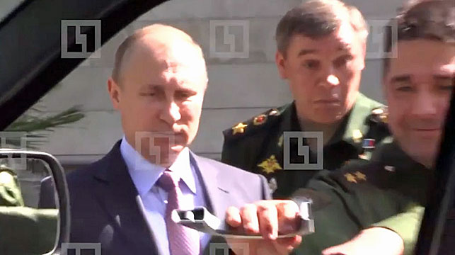 Russian President Vladimir Putin looks on as an officer rips off a car handle during a recent military inspection.