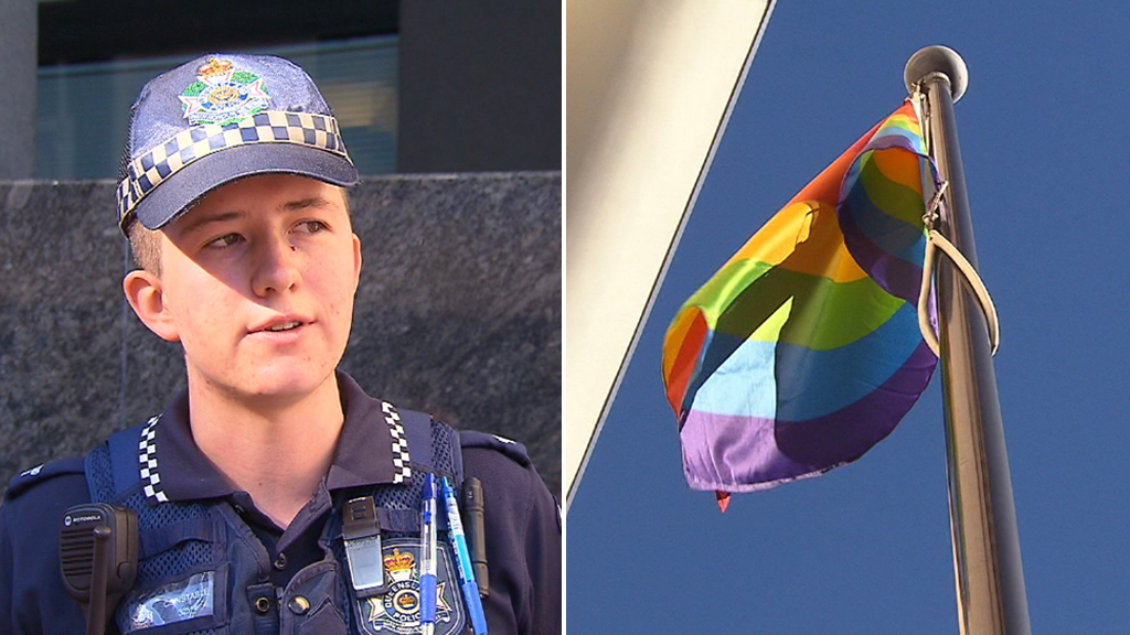 Constable Mairead Devlin, and the LGBTI flag outside the Brisbane police headquarters. (9NEWS)