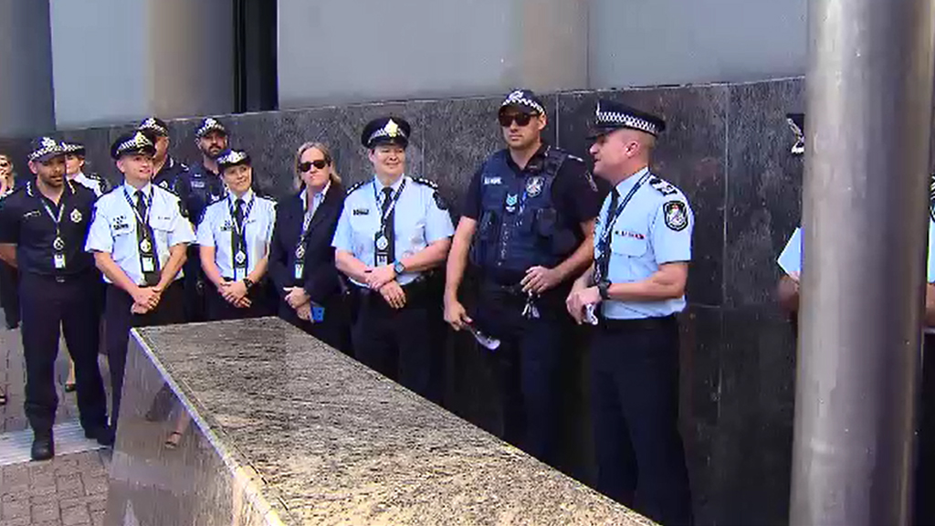 QPS LGBTI Support Network co-ordinator Sergeant Michael Gardiner (far right), with other supporters. (9NEWS)