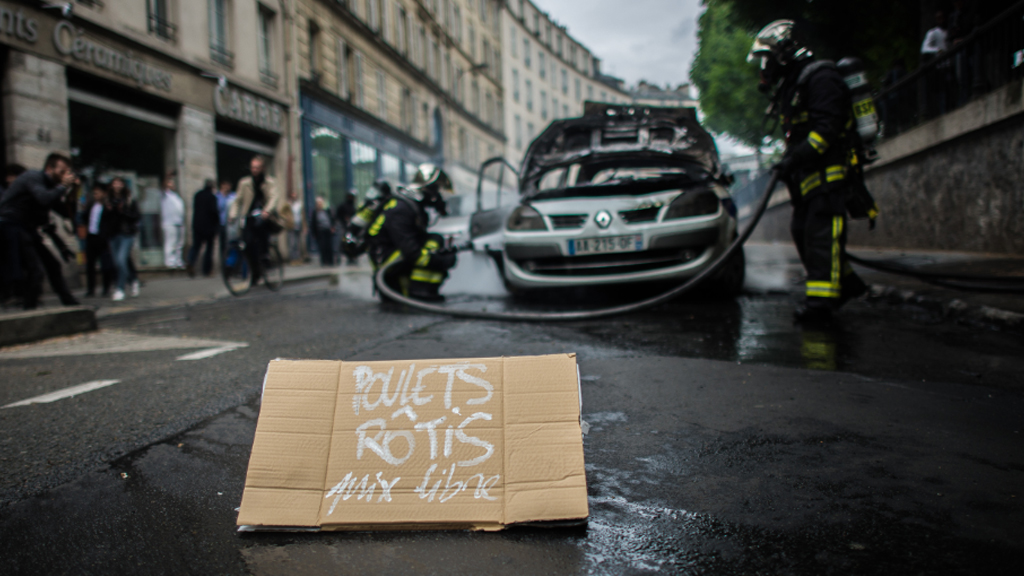 "Protesters left a sign that read ""free roast chickens"" near the burned car. (AFP)"