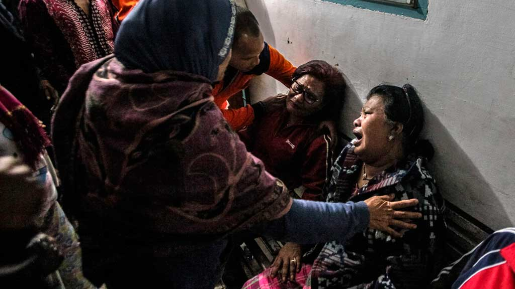 Relatives of the Mount Sinabung eruption victims cry after identifying their relatives. (AP)