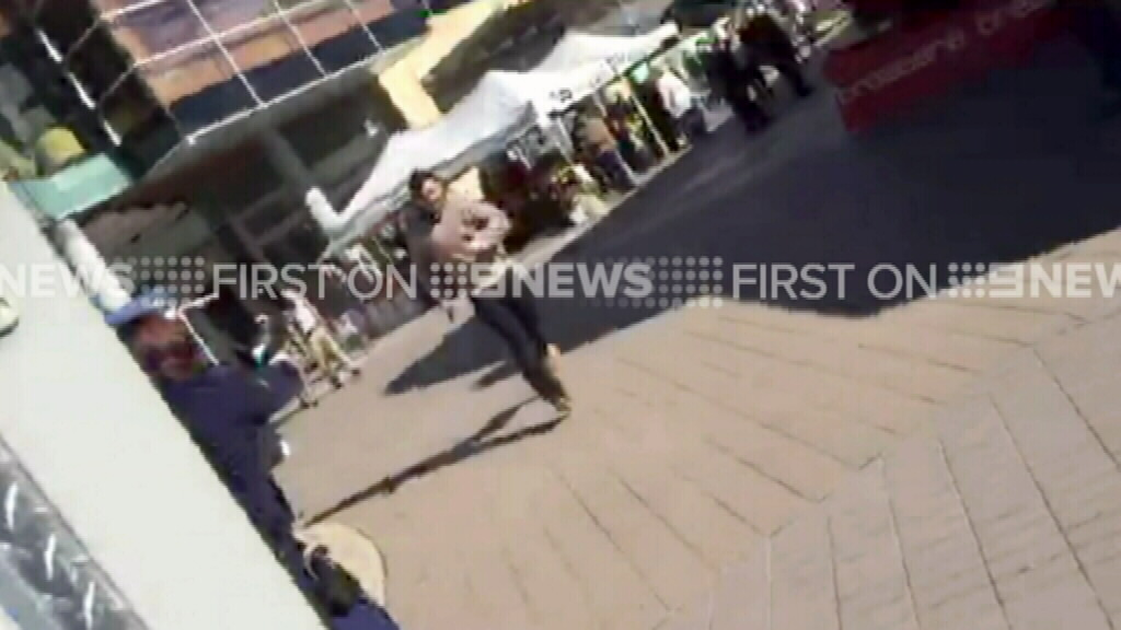The man approaches a police officer before the shooting. (9NEWS)