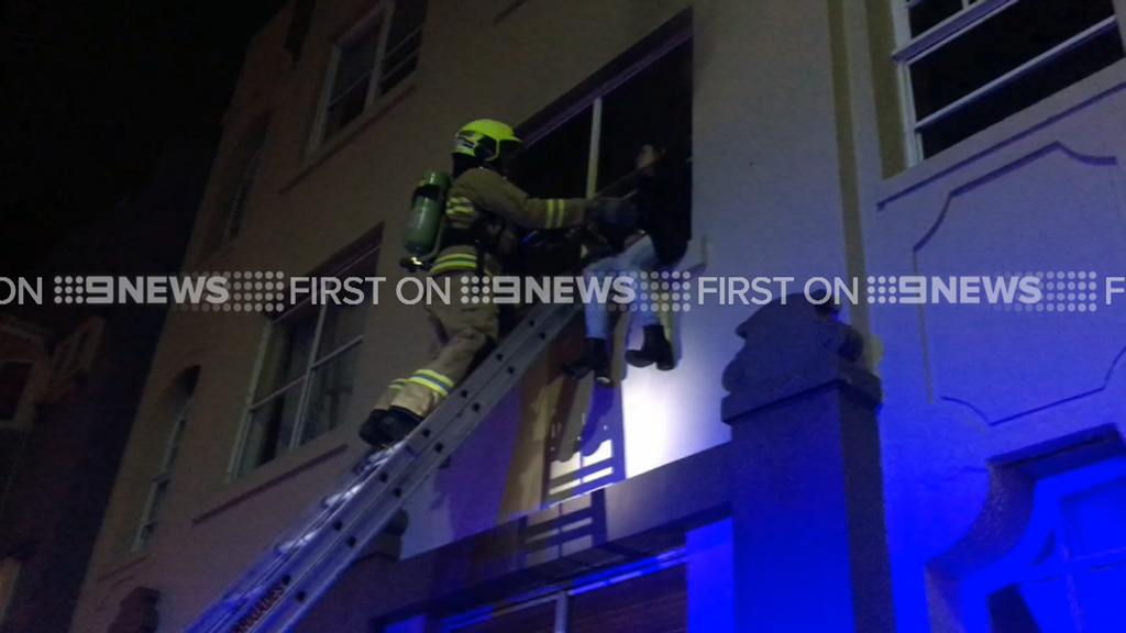 A firefighter rescues a woman from the first floor of an apartment block in Bondi.