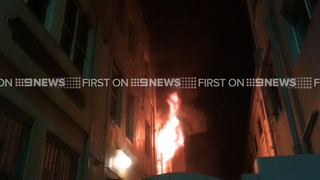 Flames escape a window at the property in Bondi. (9NEWS)