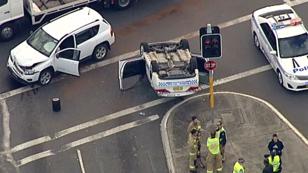 Police car rolls at intersection in Hoxton Park in Sydney's west