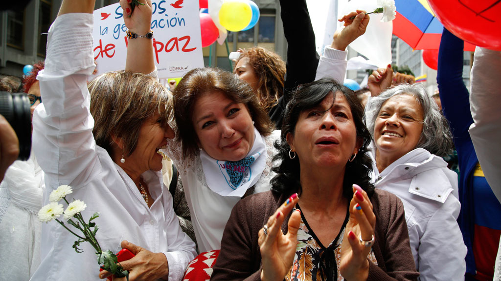People celebrate the agreement between Revolutionary Armed Forces of Colombia, FARC, and Colombia's government, in Bogota, Colombia. (AAP)