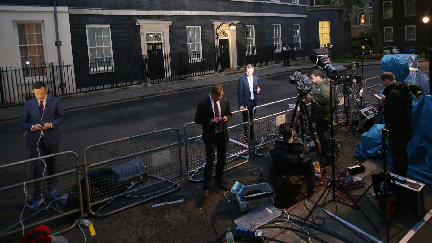 Journalists stand outside the PM's residence of 10 Downing Street as they await to hear from David Cameron. (PA Wire)