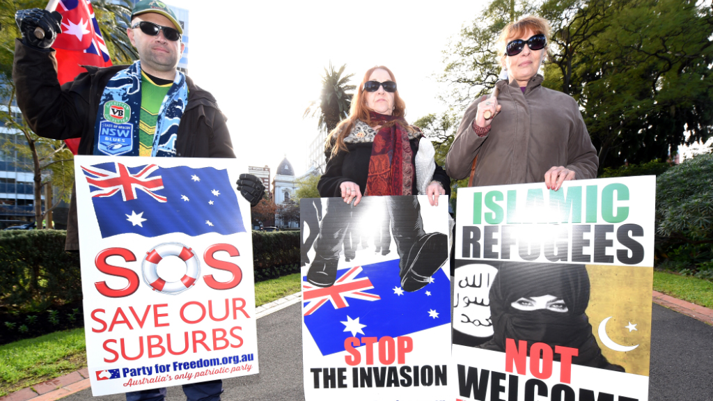 Far-right protesters held racist placards. (AAP)