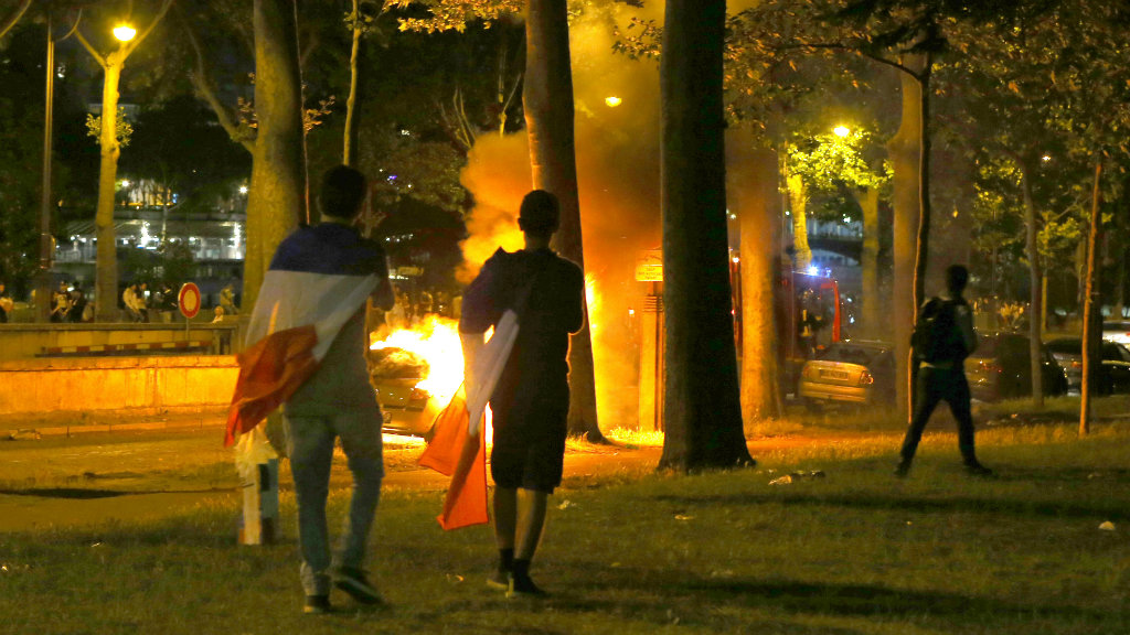 French fans near a car set alight. (AAP)