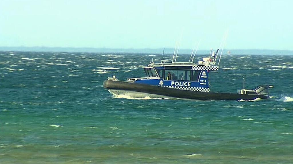 Police scour waters near where the body was found. (9NEWS)