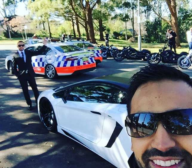 Wedding guest Ibrahim Azam in front of  sports car and the police cars blocking the street. (Instagram)