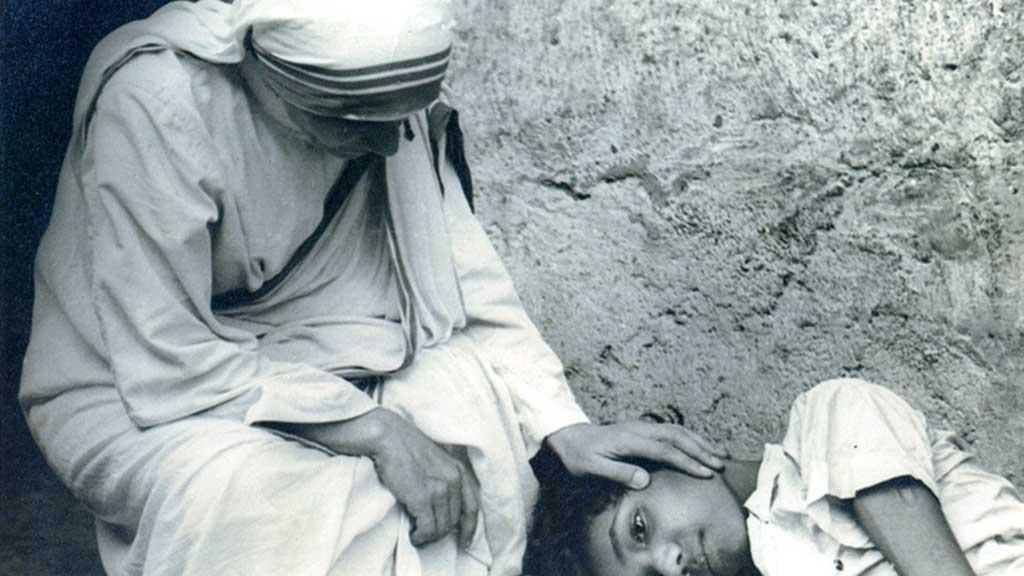 Mother Teresa comforts a sick child. (AAP)