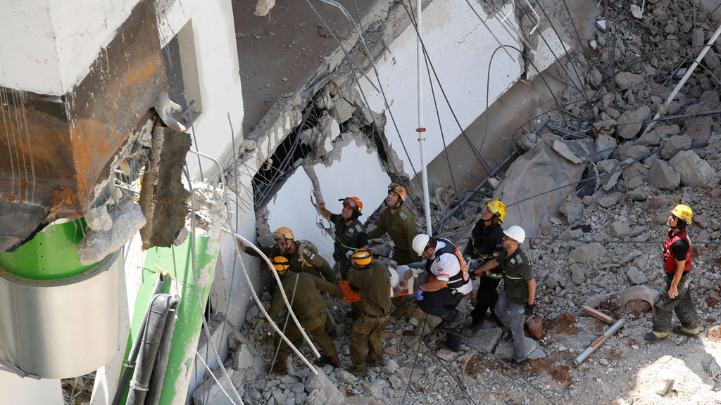 Rescuers pull a person out from the collapsed building. (AFP)
