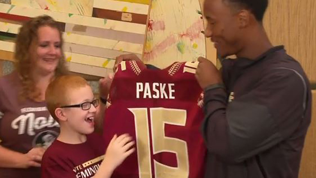 University football player gifts young fan with custom jersey after photo of the pair went viral