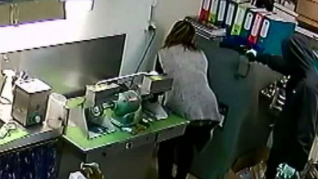 A masked offender holds a female staff member at gunpoint. (9NEWS)
