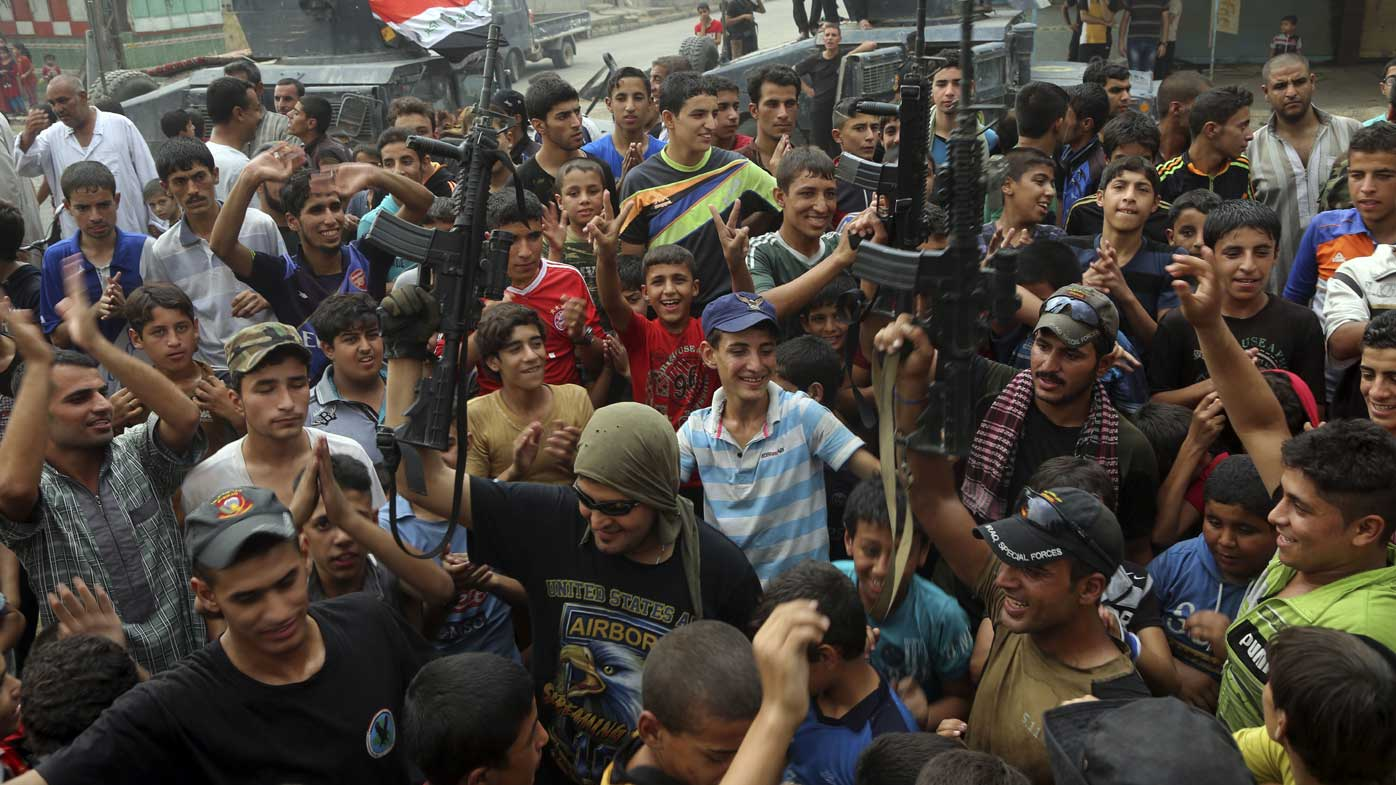 Locals in Qayara celebrate with Iraqi counterterrorism forces after the liberation of Qayara. (AP)