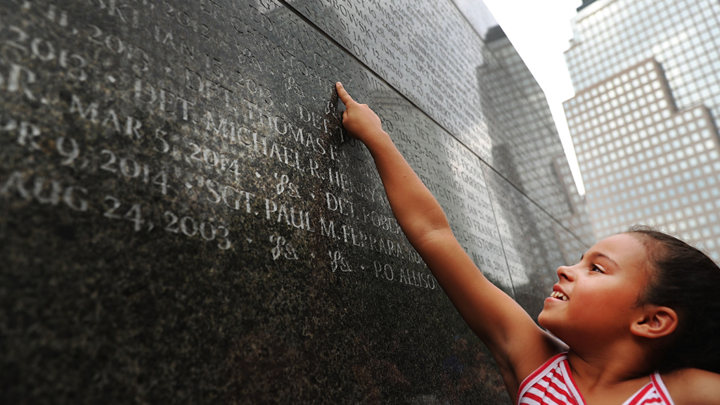 Gabriella Ortiz points to the name of her grandfather, fallen New York City police officer Edwin Ortiz at a wall commemorating officers who died during 9/11. (AFP)