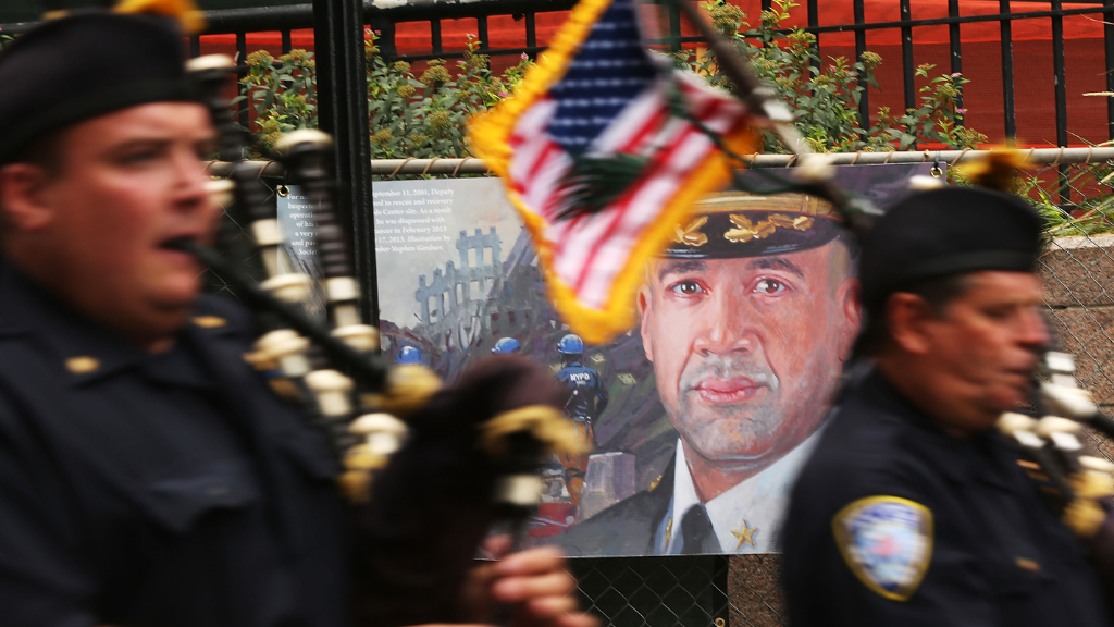 Members of the NYPD pipes and drums band pass a painting of NYPD Deputy Chief Steve Bonano, who died from a rare form of blood cancer believed to be related to his time working at Ground Zero. (AFP)